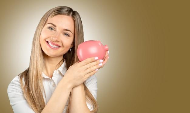 貯金箱を持つ若い女