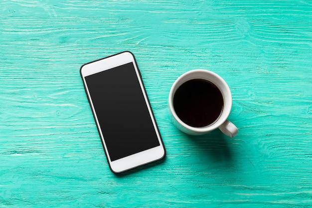 電話と木製の空白スペースにコーヒー