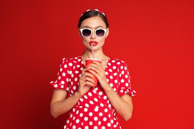 Веселая брюнетка пин-ап девушка держит безалкогольный напиток