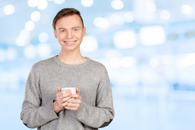 Красивый молодой человек пьет кофе
