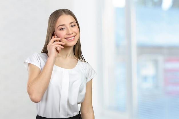 Молодая элегантная женщина разговаривает по мобильному телефону