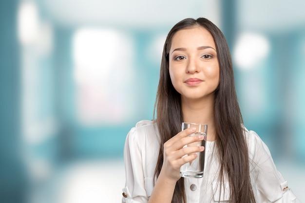 水のガラスを持つ若い女性の笑みを浮かべてください。