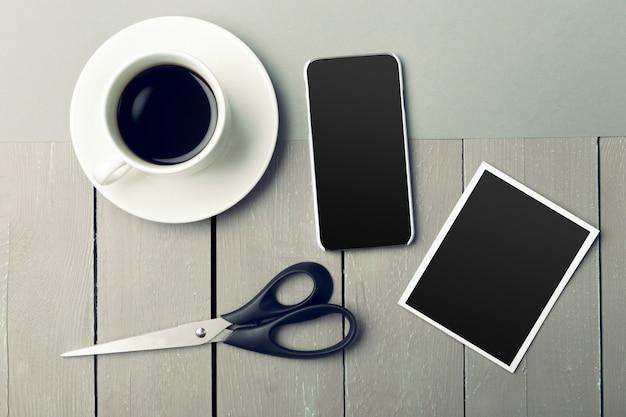 木製テーブルの上のコーヒーの横にあるスマートフォン。