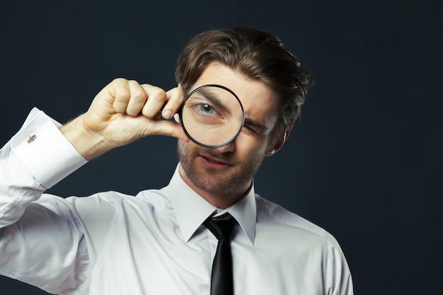 虫眼鏡を持ってビジネス男
