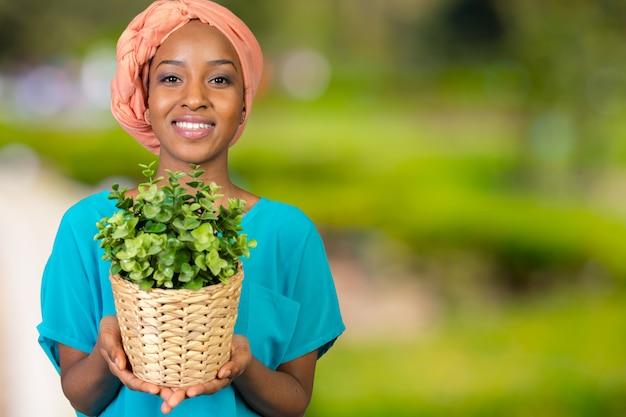 Африканская женщина держит растение в вазе