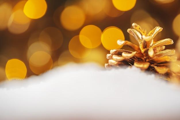 雪に覆われたテーブル、クリスマスの装飾に黄金の塗装松ぼっくり
