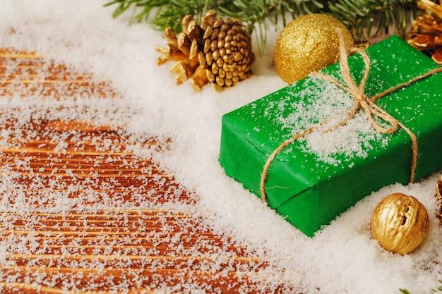 雪に覆われた木製のテーブルに飾られたプレゼントをクローズアップ