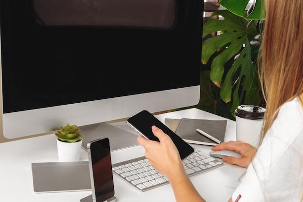 女性の手に黒い画面を持つスマートフォン。コンピューター、キーボード、事務用品、
