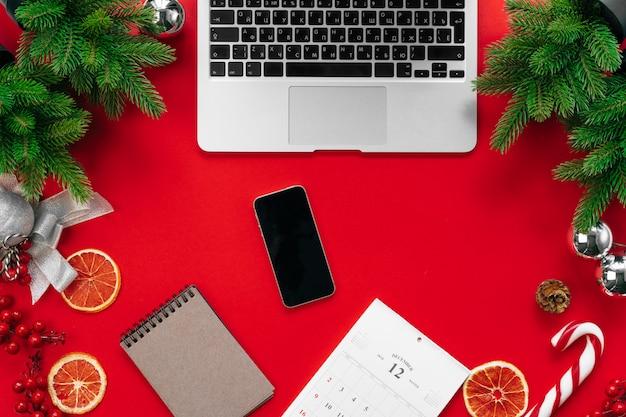 Ноутбук с еловыми ветками и елочными украшениями на красном вид сверху