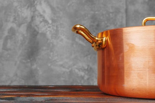 木製テーブルの上の銅の調理鍋のスタックをクローズアップ