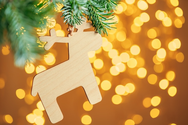 クリスマスライトに対してモミの木の枝に掛かっているクリスマスの装飾