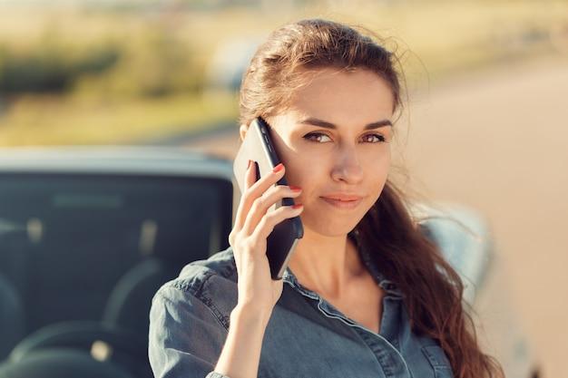 Девушка-водитель с мобильным телефоном