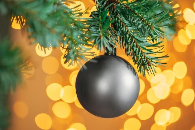 金色のボケ味の輝く灰色の安物の宝石とクリスマスツリー