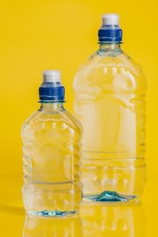 Чистая вода в пластиковой бутылке на ярко-желтом