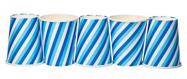 白で隔離される青い線パターンで飾られた段ボールカップ