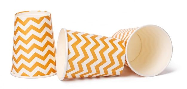 Куча картонных чашек с бежевым геометрическим рисунком на белом