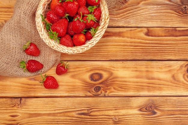 木製のテーブルにイチゴの収穫のバスケットをクローズアップ
