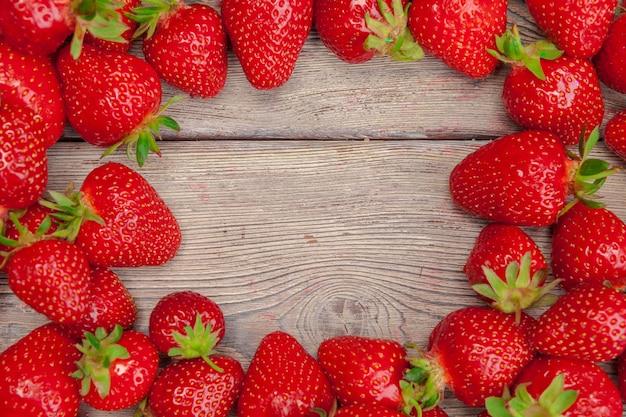 木製のテーブルに赤い熟したイチゴをクローズアップ