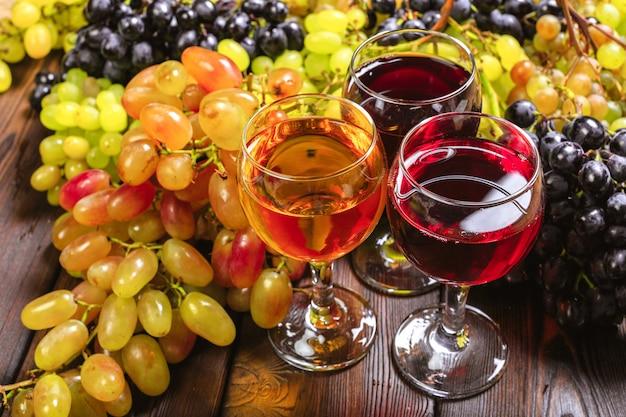 Вино с ветвями белого винограда. на деревянном столе.