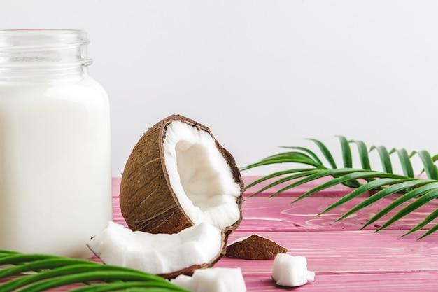 ココナッツとテーブルの上のココナッツミルクのガラス。健康食品