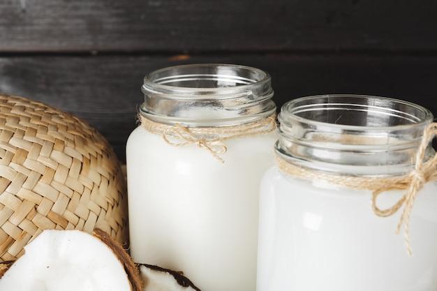 Кокосовое молоко стеклянная банка крупным планом на деревянных