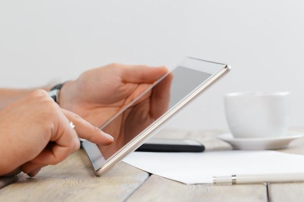 Руки человека, держащего планшетный компьютер над деревянным столом рабочей области