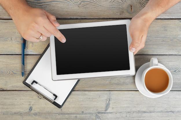 木製のワークスペーステーブルの上に空白のタブレットデバイスを置く男の手