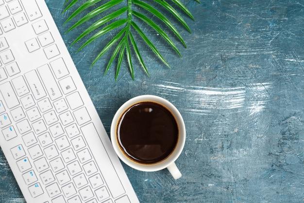 メモ用紙、コンピューターのキーボード、用品のオフィステーブルをクローズアップ