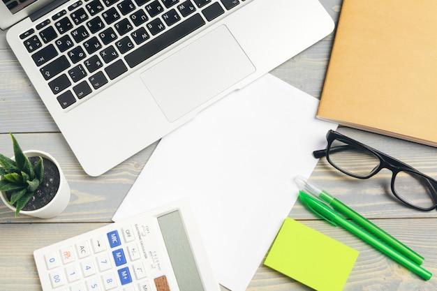 メガネと文房具の木製デスクトップのトップビューをクローズアップ。モックアップ