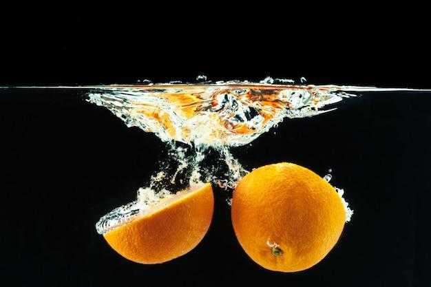 Апельсин падает в воду и делает брызги