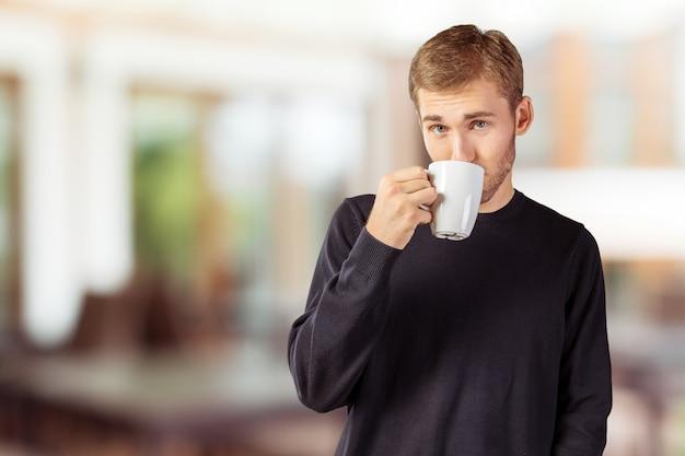 紅茶/コーヒーの暖かいカップを保持している若いハンサムな男