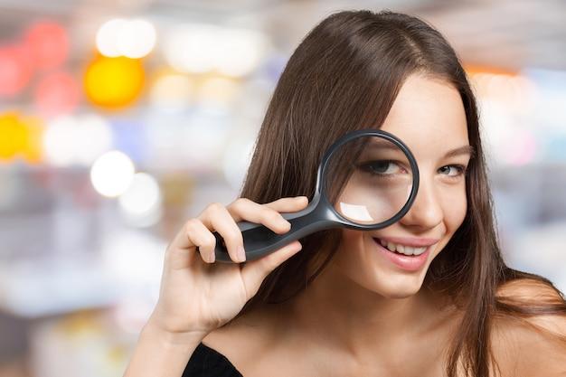 Девушка смотрит через увеличительное стекло