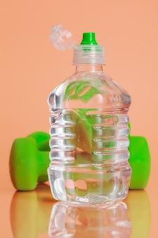 Пластиковые бутылки с водой на пастельном бежевом фоне