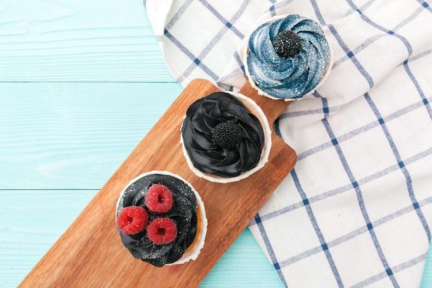 色付きの背景においしいカップケーキ。お祭りの背景、誕生日