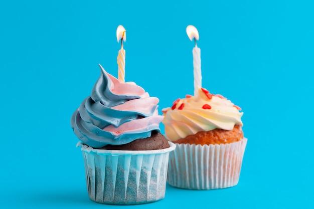 明るい色の背景にお誕生日おめでとうカップケーキ