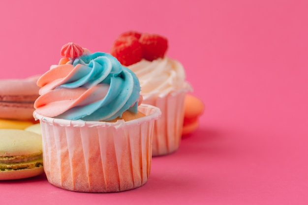 明るいピンクの背景においしい甘いカップケーキ