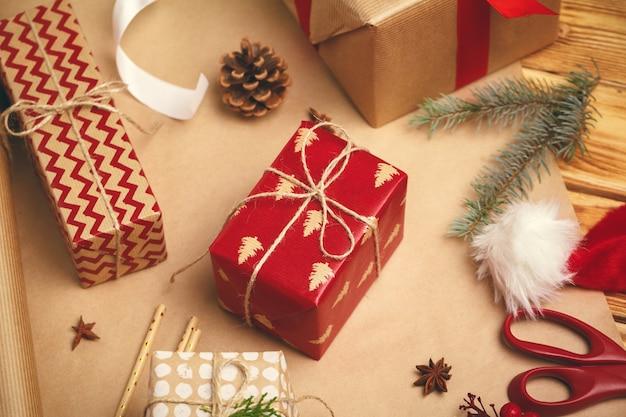 Рождественское праздничное настроение. плоский декор украшений, ленты, подарочная бумага, упакованный подарок на деревянном фоне