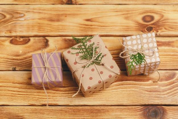木製の背景に小さなクリスマスプレゼント、上からの眺め