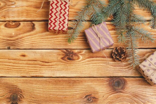 木製の背景にモミの木の枝でクリスマスプレゼント