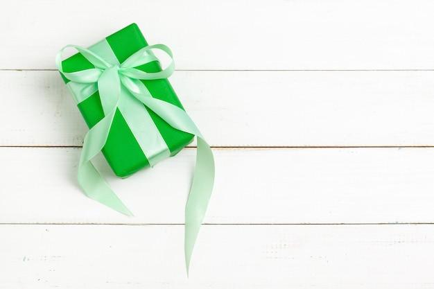 白い木製の背景上面にリボンで包まれた贈り物
