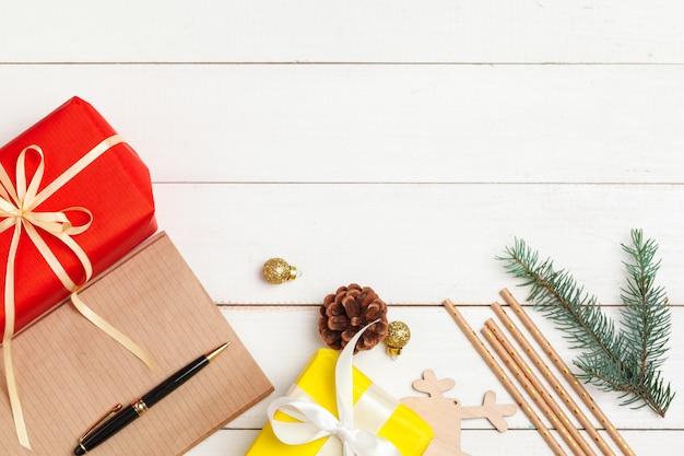クリスマスのグリーティングカードを書きます。装飾された木製のテーブルの上にペンでメモ帳を開く