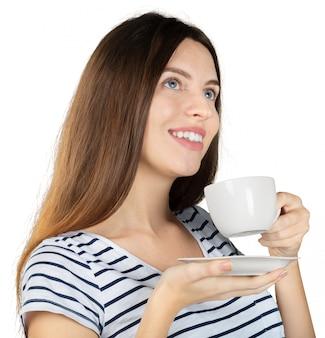 白い背景で隔離の温かい飲み物とマグカップを保持している若い女性