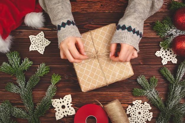 木製の背景にクリスマスプレゼントと女性の手のトップビュー