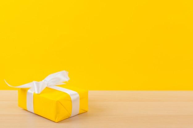 明るい黄色の背景にリボンが付いているギフト