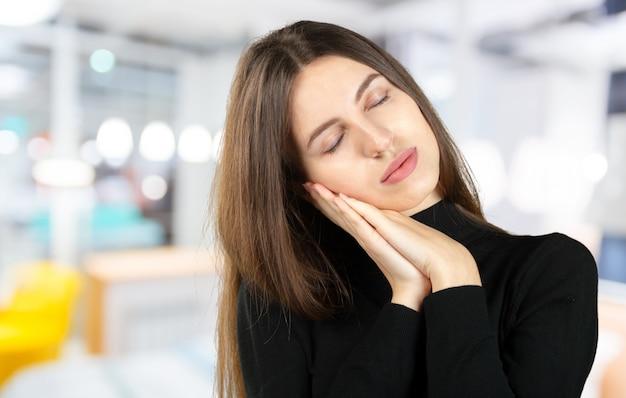 Кавказская дама притворяется спящей. молодая женщина, показывая жест сна