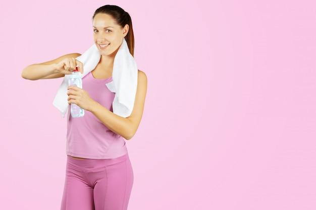 ピンクの背景の上のかなりスポーティな女の子の肖像画