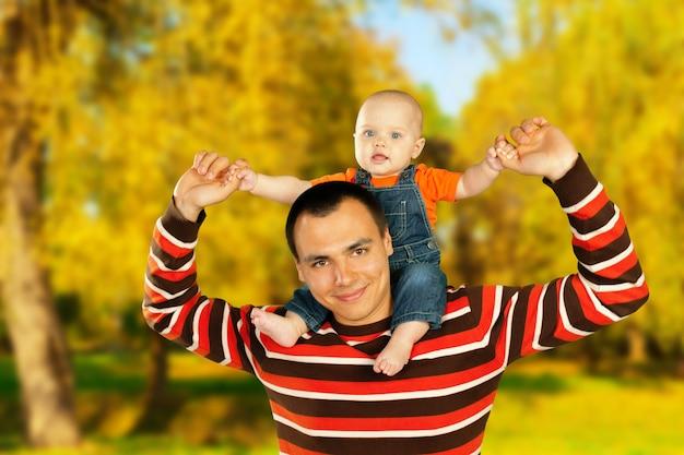 Молодой отец и его улыбающийся сын, обнимая и наслаждаясь время вместе, празднование дня отца
