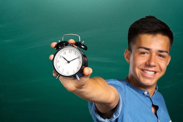 目覚まし時計を示す若い男