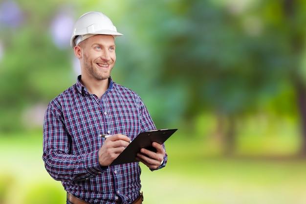 Счастливый молодой бизнесмен архитектор улыбается