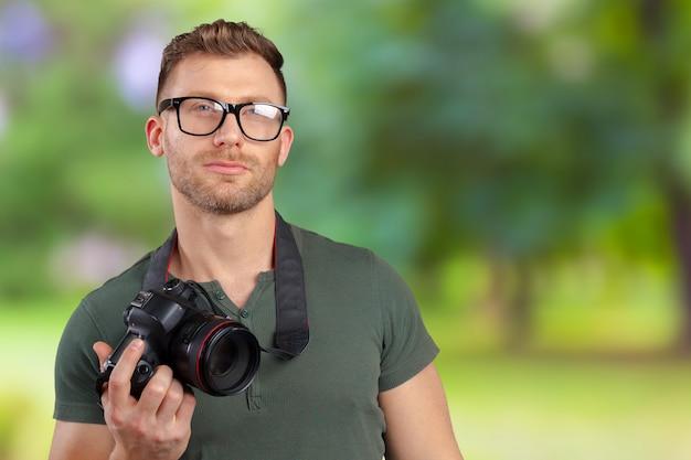 カメラを持つ眼鏡男でハンサムな若者の肖像